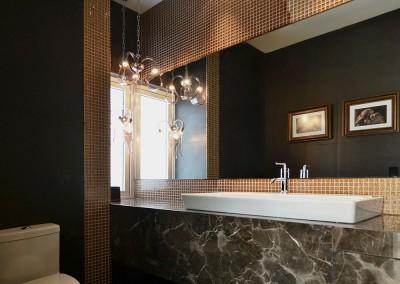 Baño social, residencia Tumbaco, negro y dorado
